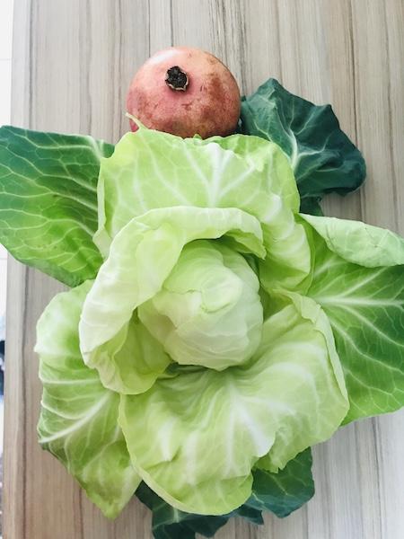 ein saftig grüner Spitzkohl und leicht rötlicher Granatapfel vor der Zubereitung